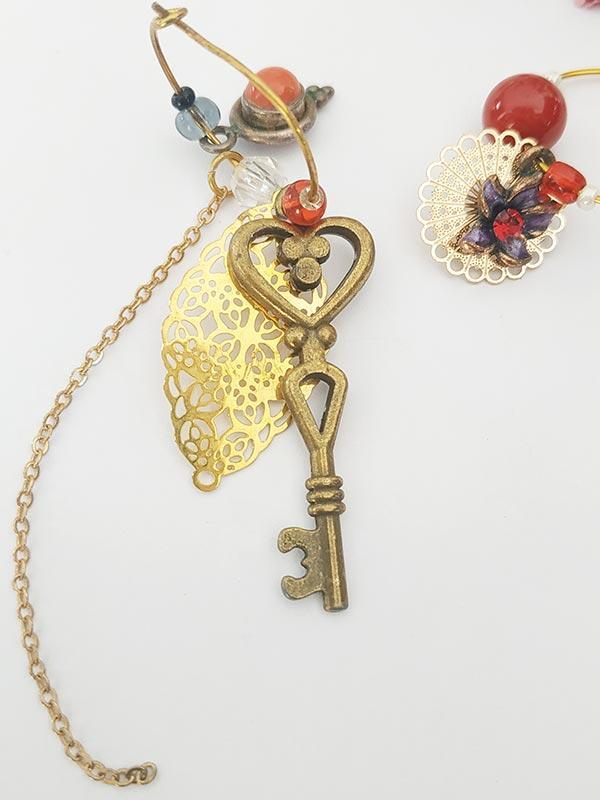 Boucles d'oreilles bijoux asymétriques estampes clé en bronze et perle rouge de FabriQémoi