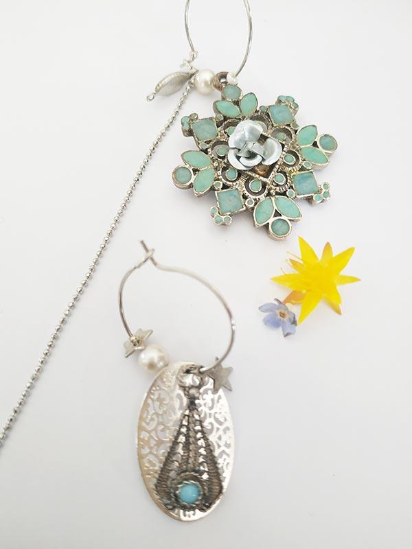 boucles d'oreilles asymétriques fait main à partir d'anciens bijoux une longue chaîne avec un pendentif étoile vert d'eau et l'autre estampe argent tenue par des créoles argentées de FabriQémoi